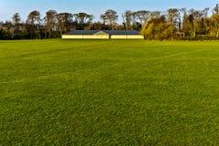 Voetbalhof met groene gras dag leeg stock afbeeldingen