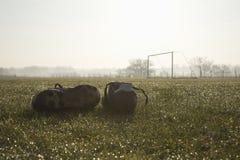 Voetballaarzen op een lege voetbalhoogte Stock Afbeeldingen