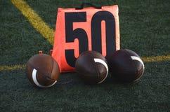 Voetballen bij 50 yardlijn stock afbeelding