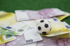 Voetballen en muntnota's op kunstmatig gras worden geschikt dat Stock Afbeeldingen