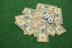 Voetballen en muntnota's over kunstmatig gras Stock Afbeelding