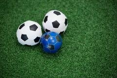 Voetballen op kunstmatig gras Stock Foto
