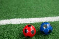 Voetballen op kunstmatig gras Stock Afbeeldingen