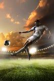 Voetballer in actie betreffende de achtergrond van het zonsondergangstadion Stock Foto
