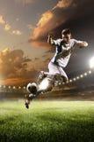 Voetballer in actie betreffende de achtergrond van het zonsondergangstadion Stock Foto's