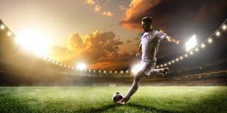 Voetballer in actie betreffende het panoramaachtergrond van het zonsondergangstadion royalty-vrije stock foto's