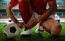 Voetballer bindende schoenen op het gebied stock fotografie