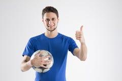 Voetballer blauw overhemd met bal geïsoleerde studio stock afbeelding
