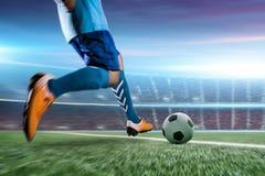 Voetballer in de bal van de actieschop bij stadion Stock Foto