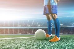 Voetballer in de bal van de actieschop bij stadion Royalty-vrije Stock Afbeeldingen