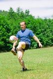 Voetballer die de bal schopt Stock Foto