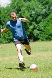 Voetballer die de bal schopt Royalty-vrije Stock Afbeeldingen