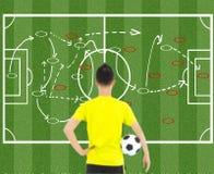 Voetballer die een bal houden en aanvalstactiek denken Stock Foto's