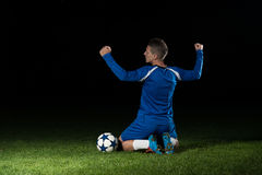 Voetballer die Victory On Black Background vieren Stock Afbeelding