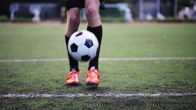 Voetballer het spelen met bal op gebied stock footage
