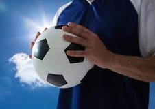 voetballer met bal op zijn handen met een blauwe hemel Royalty-vrije Stock Afbeelding