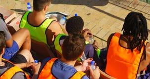 Voetballers die in het stadion op een zonnige dag 4k zitten stock videobeelden