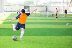 Voetballersnelheid in werking om wordt gesteld om bal aan doel op kunstmatig gras te schieten dat stock foto's
