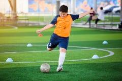 Voetballersnelheid in werking om wordt gesteld om bal aan doel op kunstmatig gras te schieten dat stock fotografie