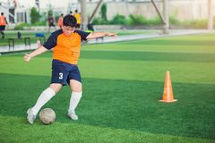 Voetballersnelheid in werking om wordt gesteld om bal aan doel op kunstmatig gras te schieten dat stock afbeelding