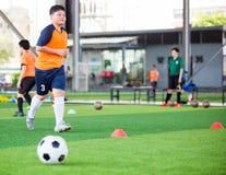 Voetballersnelheid in werking om wordt gesteld om bal aan doel op kunstmatig gras te schieten dat stock afbeeldingen