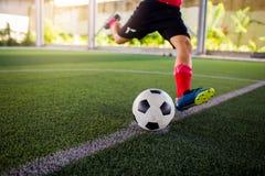 Voetballersnelheid in werking om wordt gesteld om bal aan doel op kunstmatig gras te schieten dat royalty-vrije stock afbeeldingen