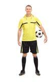 Voetbalscheidsrechter in geel Jersey die een bal houden Stock Afbeelding