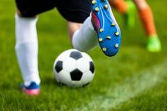 Voetbalschop Voetballer Kicking Ball op Grashoogte De voetbalvoetballer raakt een Bal stock foto