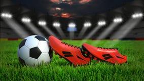 Voetbalstadion met bal en schoenen stock fotografie