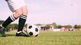 Voetbalster die de bal schopt stock footage