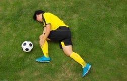 Voetbalster liggen verwond op de hoogte stock foto