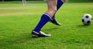 Voetbalster speelvoetbal op het gebied stock video