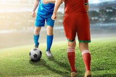 Voetbalstermens die de bal druppelen die aan voorbij zijn tegenstander proberen stock afbeelding
