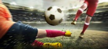 Voetbalstermens die de bal schoppen wanneer zijn tegenstander die de bal proberen aan te pakken stock foto