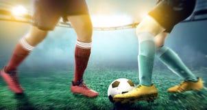 Voetbalstervrouw die de bal rollen wanneer het behandelen van haar tegenstander stock fotografie