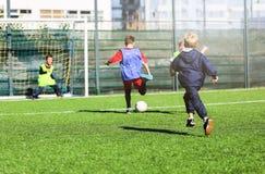 Voetbalteam - jongens in rood en blauw, groen eenvormig spelvoetbal op het groene gebied Teamspel, opleiding, actieve levensstijl stock afbeeldingen