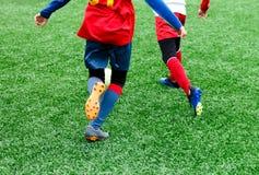 Voetbalteams - jongens in rood, blauw, wit eenvormig spelvoetbal op het groene gebied jongens het druppelen Teamspel, opleiding,  royalty-vrije stock afbeelding