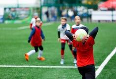 Voetbalteams - jongens in rood, blauw, wit eenvormig spelvoetbal op het groene gebied jongens het druppelen het druppelen vaardig royalty-vrije stock foto's