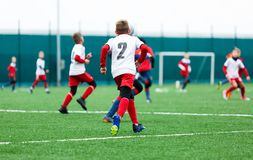 Voetbalteams - jongens in rood, blauw, wit eenvormig spelvoetbal op het groene gebied jongens het druppelen het druppelen vaardig stock fotografie