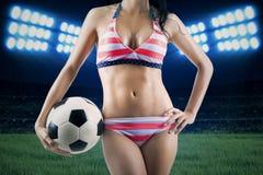 Voetbalventilator die bikini dragen en bal houden stock afbeelding