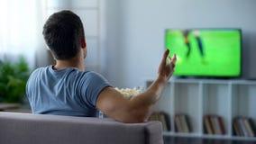 Voetbalventilator die popcorn eten, kritiserend spelers op TV, die onderwijzen hoe te noteren stock foto