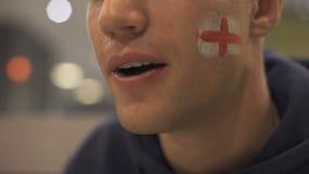 Voetbalventilator met Engelse die vlag op wang het letten op gelijke enthousiast wordt geschilderd stock video