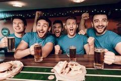 Voetbalventilators die op het spel het drinken bier letten en het eten bij sportenbar stock fotografie