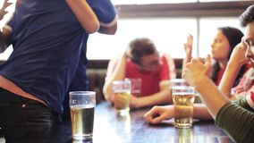 Voetbalventilators die op voetbalwedstrijd letten bij bar of bar stock video