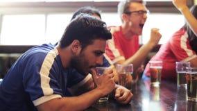 Voetbalventilators die op voetbalwedstrijd letten bij bar of bar stock videobeelden