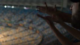 Voetbalventilators die spelers boe roepen bij stadion, ontevreden met slow-motion spel, stock videobeelden