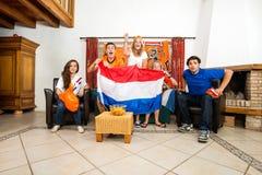 Voetbalventilators die terwijl thuis het Letten van op Gelijke toejuichen Stock Fotografie