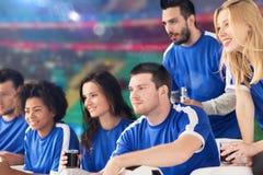 Voetbalventilators die voetbal op gelijke letten bij stadion Stock Afbeelding