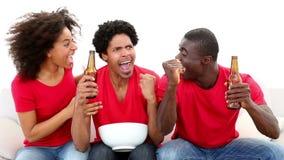 Voetbalventilators in rode zitting bij laag het toejuichen stock footage