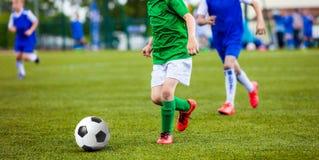 Voetbalvoetbalwedstrijd Jonge geitjes die Voetbal spelen Young Boys die Voetbal schoppen Stock Foto's